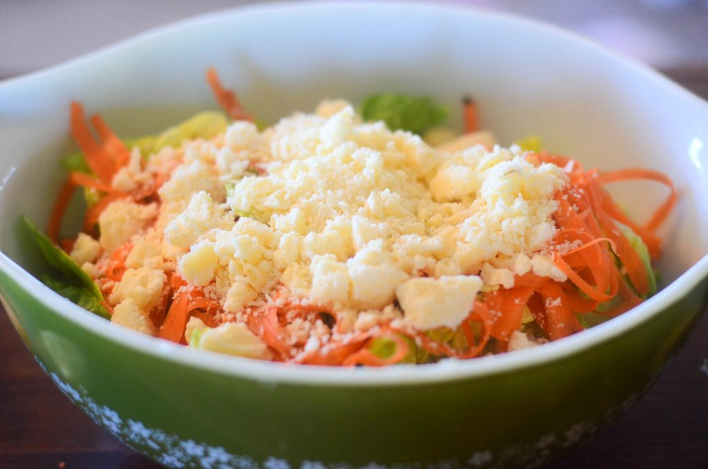 salad in a green bowl with crumbled cheese on top