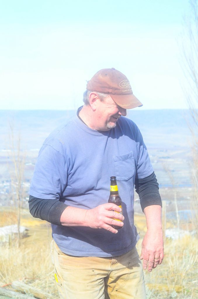 fence builder sipping beer and laughing