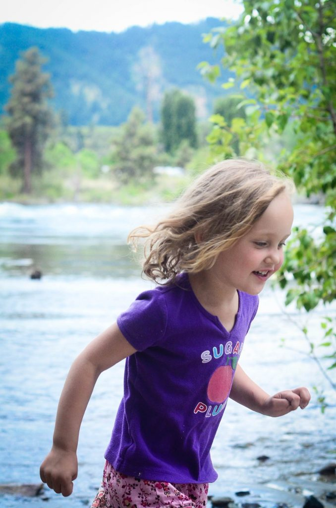 blonde little girl playing near a river